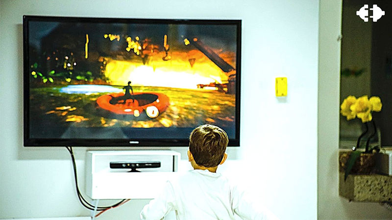 A kid playing video game on a IPS panel television.